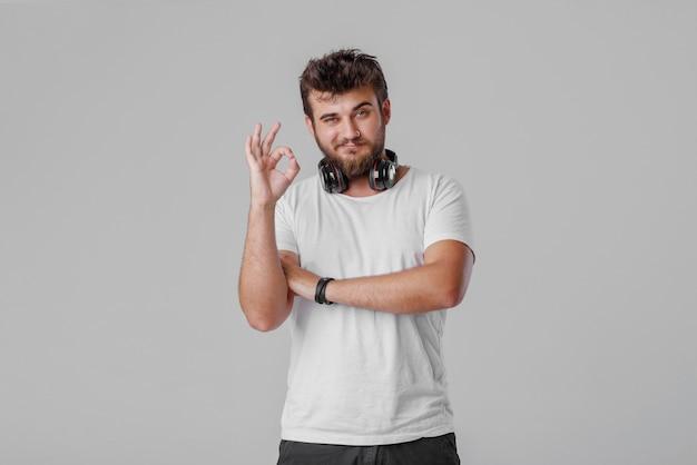 Молодой человек с бородой с беспроводными наушниками на шее. ок жестами пальцами