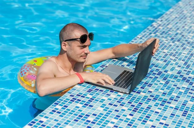 Молодой человек на летние каникулы с ноутбуком, бизнес в интернете. дистанционный домашний офис в бассейне в резиновом кольце на карантине
