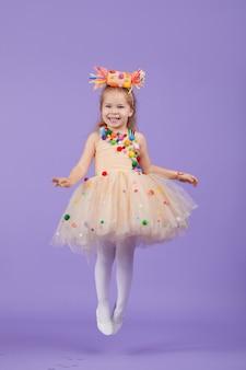 子供の誕生日パーティー、仮面舞踏会。紫のスペースで楽しんで、ふくらんでいるチュチュデザインの凝った服で少し幸せな幼児子供女の子。テキストのためのスペース