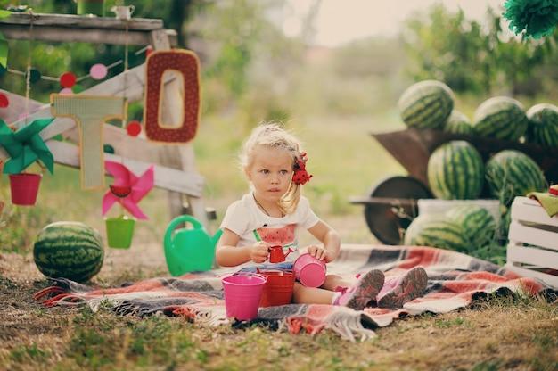 Маленькая девочка в красном платье сидит в саду возле арбуза