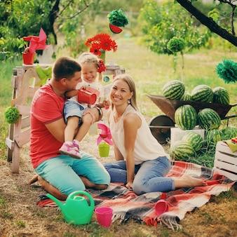 Молодые родители играют с маленьким ребенком в саду