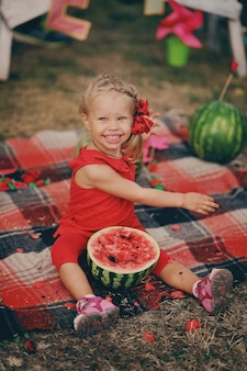 Маленькая девочка в красном платье сидит в саду и ест арбузы