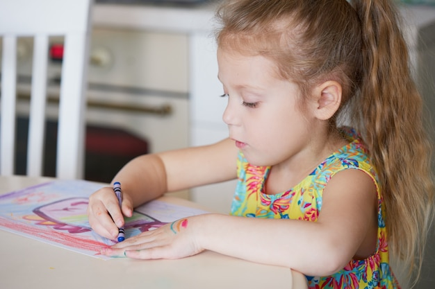 子供の創造性。子供の女の子が自宅でワックス鉛筆で描画します。世界的な検疫期間中のオンライン遠隔教育の概念。