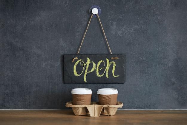 黒いチョークボードにある「カフェで開く」と書かれた看板。隔離後。暗い空間でテイクアウトのコーヒーグラス。開業