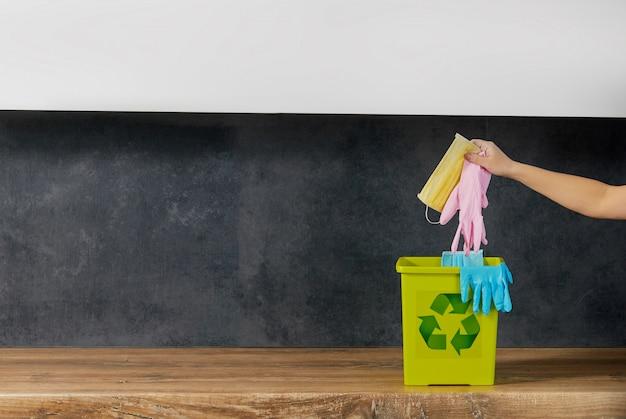コロナウイルス隔離の終わり。女性の手が使用済みのフェイスマスクと手袋をゴミ箱に捨てます。通常の生活に戻る
