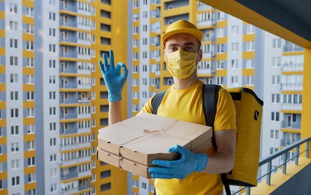 安全な食品配達。黄色の制服を着た宅配便、保護マスクと手袋がコロノウイルスの検疫中に持ち帰り用の食品を届けます