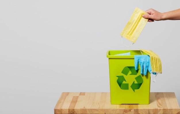 コロナウイルス検疫の終わり。女性の手は、使用済みのフェイスマスクをゴミ箱に投げます。通常の生活に戻る