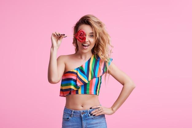 Веселая позитивная веселая привлекательная дама со своими стильными модными вьющимися волосами, держит сахарную присоску на палочке, изолированную на розовом
