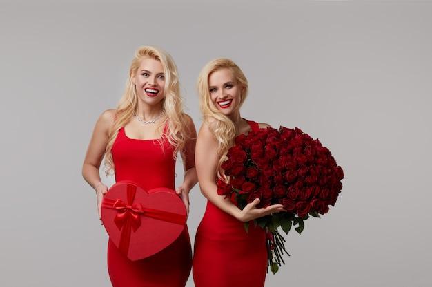 Две счастливые молодые женщины-близнецы с большим букетом красных роз и красной коробкой в форме сердца.