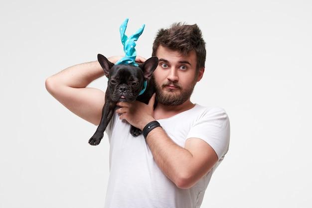 ヒップスターのひげを生やした男が素敵なフレンチブルドッグ犬を抱きしめて愛と抱きしめ、彼と遊んで