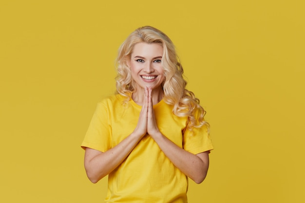 黄色の壁を越えて立っている幸せな若いブロンドの女性の写真