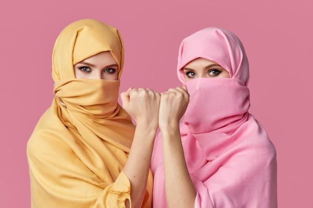 Две молодые мусульманские арабские женщины в ярких хиджабах на розовой стене
