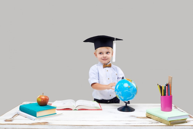 灰色の孤立した壁に卒業の帽子をかぶっている男の子は勉強しています