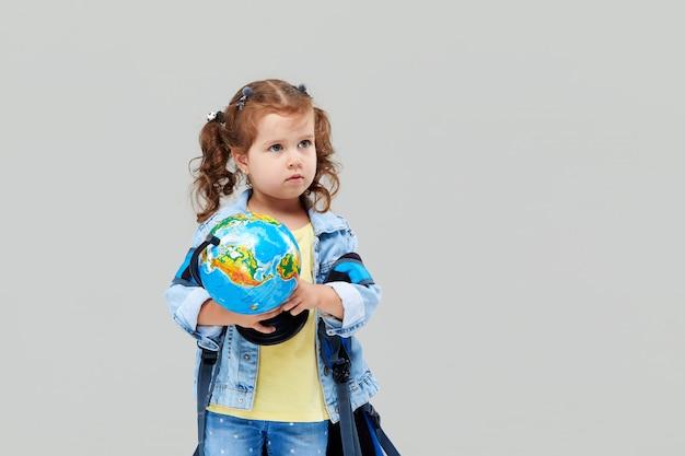 Милая дошкольная девушка с синим рюкзаком на спине, держа в руках глобус