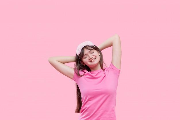 あくびとピンクに分離された目覚まし時計を保持しているアイマスクを眠っている若いアジア女性。眠れない夜