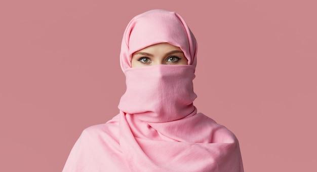 Портрет молодой мусульманской аравийской женщины нося красочный хиджаб. указывает пальцем в сторону.