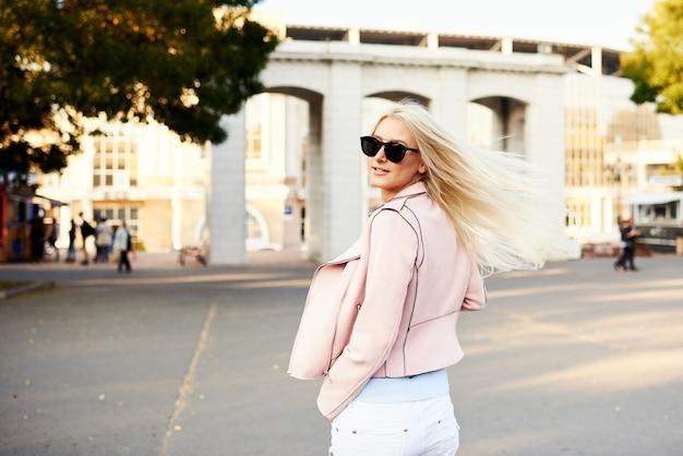 ストリートファッションのコンセプト。日当たりの良い公園を歩いてスタイリッシュな少女学生と行くコーヒーのカップを保持しています。