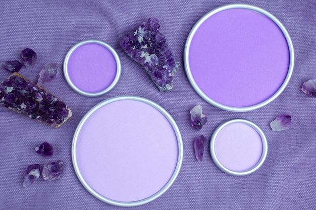 紫の布地にデザイナーのテキストを配置するための円形フレームのアメジストクリスタル。フラットレイ