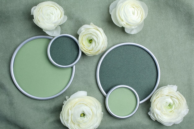 緑の布地にデザイナーのテキストを配置するための円形フレームのラナンキュラスの花。フラットレイ