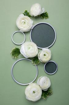 緑のデザイナーのテキストのための場所が付いている円形フレームが付いているラナンキュラスの花。フラットレイ