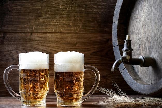 木製樽の横にある大きなビールジョッキ