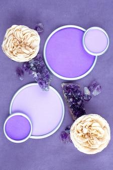 紫の布地にデザイナーのテキストを配置できる円形フレームのアメジストクリスタルとバラ。フラットレイ