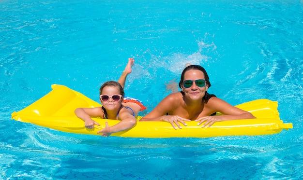 幸せな少女とプールで母