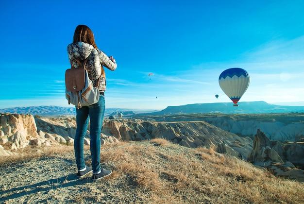 Женщина турист, принимая фотографии воздушного шара в каппадокии