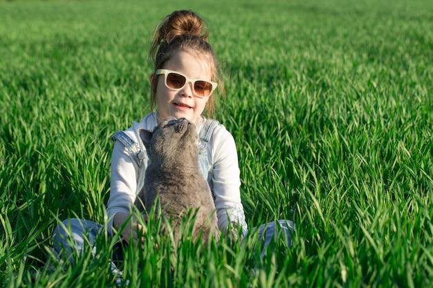 Девочка маленького ребенка, с удовольствием с кошкой в саду