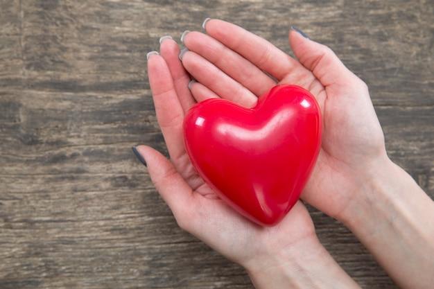Красное сердце в руках