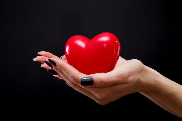 Красное сердце в руке человека