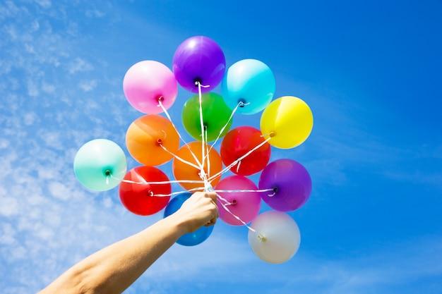 青い空に風船を持っている人