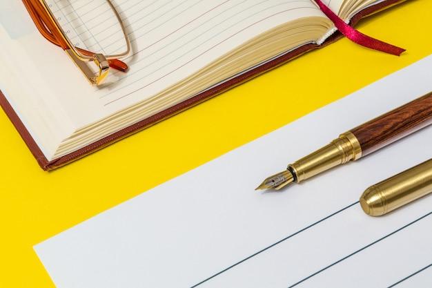 金色のペンとガラスの黄色のテーブルの上のオフィスの静物はノートの準備中です