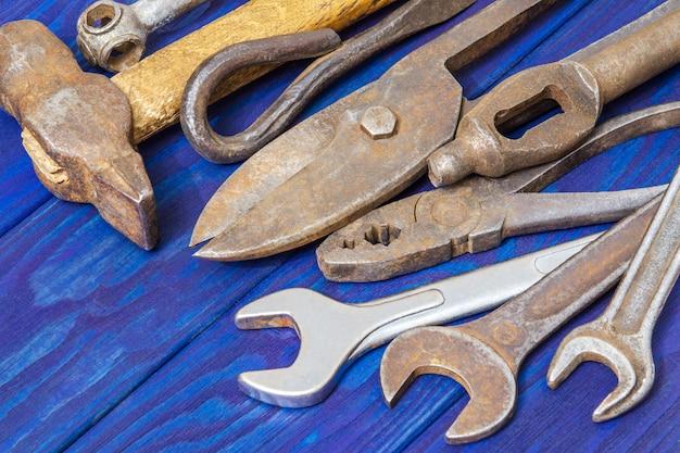 青いヴィンテージの木製ボードでの作業後に積み上げられた多くの異なる古いツール