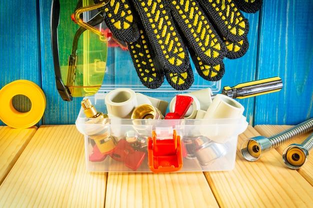 Ручные инструменты для сантехники и частей на деревянных фоне с пространством для рекламы.