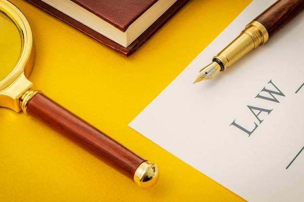 法律とメモ帳にペンで黄色のテーブルの上のオフィスの静物