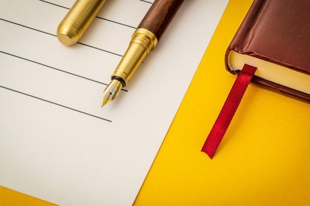 シートとメモ帳にペンで黄色のテーブルにオフィスのある静物