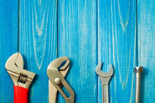 青い木製のテーブルの配管工のためのツールの大きなセット。
