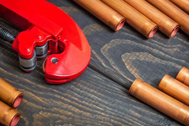赤いパイプカッターと配管修理用コネクタ付き銅パイプ