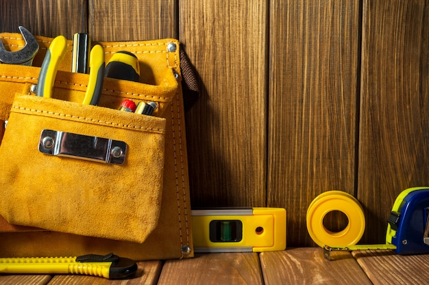ツールと木製の壁にレザーバッグの楽器