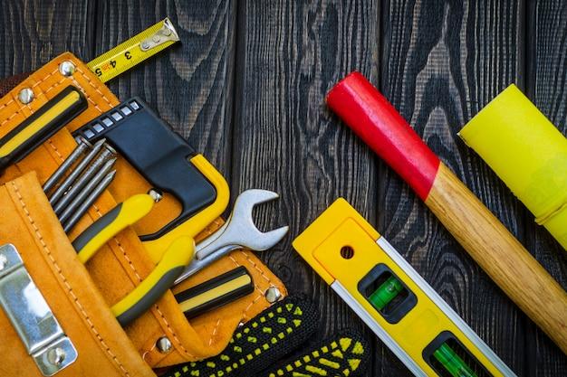 木製の黒板に大工仕事とアクセサリーのためのバッグのツール