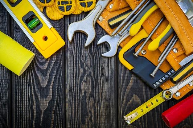木製の暗い板に大工仕事とアクセサリーのためのバッグの中の道具