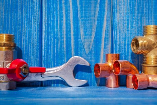 青いヴィンテージの木製ボードの配管修理用のスペアパーツ、ツール、アクセサリー
