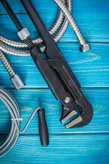 青い木の板にマスター配管工に必要な工具とホースのセット