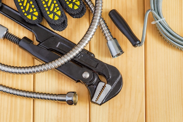 木の板の配管工に必要な工具とホースのセット