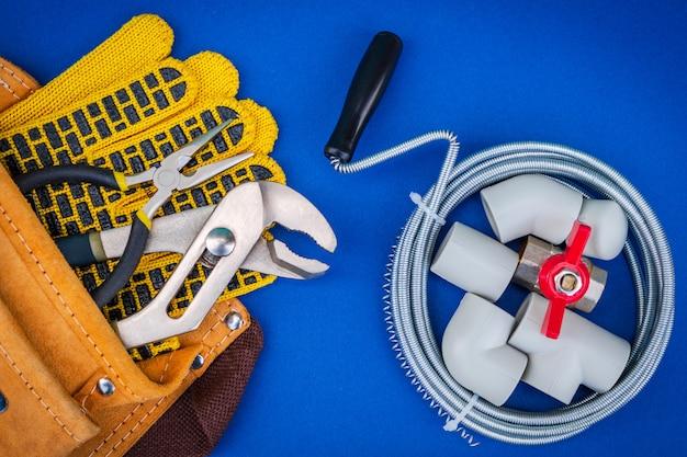 配管ツールと青色の背景に水ホースを接続するための手袋