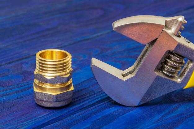 スペアパーツの修理または交換中の真ちゅう製の真ちゅう継手と青い木の板の調整可能なスパナのクローズアップ