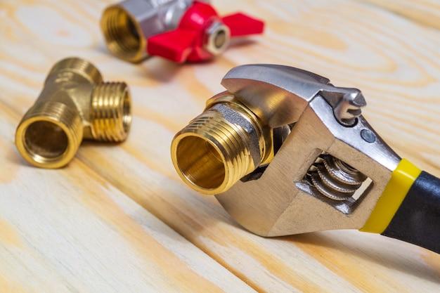 スペアパーツの修理または交換時に木の板に配管継手と調整可能なスパナのクローズアップ
