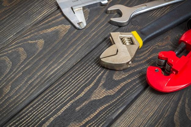 修理や建設の前にプロのマスターによって準備された黒のヴィンテージ木の板に配管工のためのツールの大きなセット