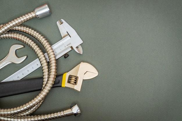 修理または建設の前にプロのマスターが準備した暗いワークショップテーブルのツールとホースの大きなセット